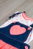 珊瑚和蓝色礼服,有心脏的总体在灰色木背景 小女孩成套装备 关闭 免版税库存图片