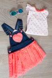 珊瑚和蓝色礼服,有顶面近的太阳镜的总体在灰色木背景 小女孩成套装备 视图 库存照片