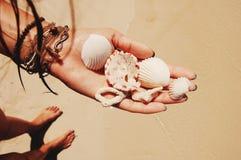 珊瑚和贝壳在手中与镯子 库存照片