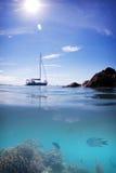 珊瑚礁鱼小船太阳水和天空 免版税图库摄影