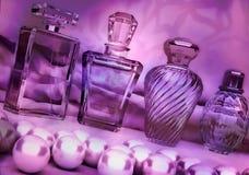 珍珠和不同的瓶在黑暗的紫色backgroun的香水 免版税库存图片