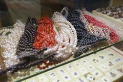 珍珠和珊瑚五颜六色的串在金银手饰店 免版税库存照片