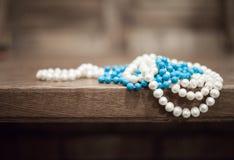 珍珠和绿松石小珠从桌的边缘垂悬 免版税图库摄影