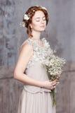 珍珠灰色礼服的年轻红发新娘 她站立,她的眼睛是梦想闭合的,她拿着白色野花花束  库存照片
