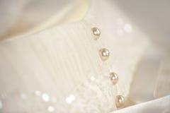 珍珠线在一套白色婚礼礼服按 免版税库存照片