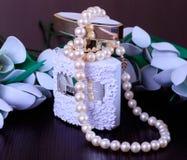 珍珠项链和香水在花背景 免版税图库摄影