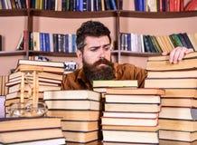 珍藏书籍者概念 老师或学生有胡子的坐在桌上与书, defocused 之间有希望的面孔的人 图库摄影