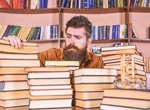 珍藏书籍者概念 老师或学生有胡子的坐在桌上与书,defocused 之间有希望的面孔的人 免版税图库摄影