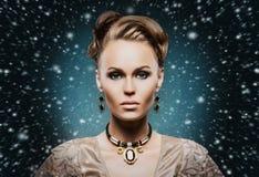 珍贵的首饰的年轻和美丽的夫人在雪 免版税库存照片