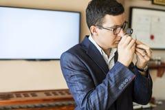 珠宝商审查的金刚石通过寸镜 免版税图库摄影
