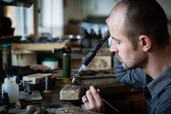 珠宝商银色焊接在他的车间 免版税库存照片