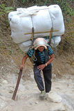 珠穆琅玛阵营,国家公园,尼泊尔- 4月15 2017年 运载重的大袋的夏尔巴搬运工 图库摄影