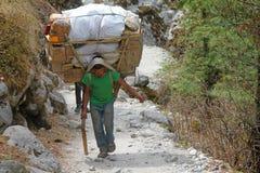 珠穆琅玛阵营,国家公园,尼泊尔- 4月15 2017年 运载重的大袋的年轻sherpa搬运工 免版税库存图片