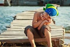 班丹纳花绸的男孩坐木桥在沙子晴朗的夏日 免版税库存照片