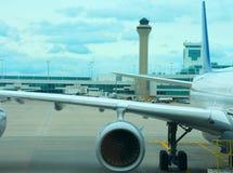 班机在柏油碎石地面的飞机特写镜头与空中交通管理塔在背景中 免版税图库摄影