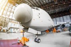 班机航空器在有起重器的一个飞机棚站立 图库摄影