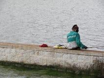班格洛,卡纳塔克邦,印度- 2009 9月5日A通过使用一根木钓鱼竿的人渔在Ulsoor湖 免版税库存图片