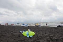 球、游泳的玻璃、凉鞋、水滑行车和浮动圆环在海滩 沙子的被弄脏的人靠岸,覆盖,涌起 免版税库存图片
