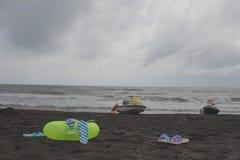 球、游泳的玻璃、凉鞋、水滑行车和浮动圆环在海滩 阴云密布,浪涌 库存照片