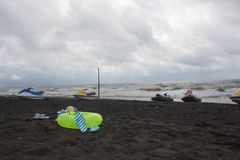 球、游泳的玻璃、凉鞋、水滑行车和浮动圆环在海滩 阴云密布,浪涌 图库摄影