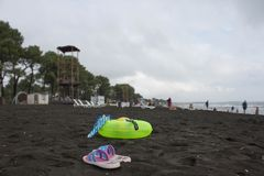 球、游泳的玻璃、凉鞋和浮动圆环在海滩 使生活,图象期望迷离,阴云密布的海滩的游人靠岸 库存照片