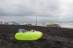 球、游泳的玻璃、水滑行车和两浮动圆环在海滩 沙子海滩的被弄脏的人 旅行或海假期concep 免版税库存照片