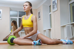 球健身女孩体操坐的排球 库存图片