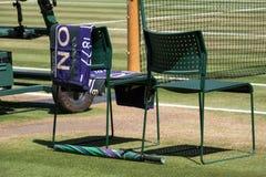 球员与毛巾的`椅子重叠了后面和一把绿色和紫色伞在地面上 毛巾有对此的名字德约科维奇 免版税库存图片