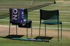 球员与毛巾的`椅子重叠了后面和一把绿色和紫色伞在地面上 毛巾有对此的名字德约科维奇 免版税图库摄影