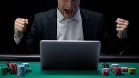 球员赌博在膝上型计算机和尖叫在兴奋,赢得的赌注,时运 免版税库存照片