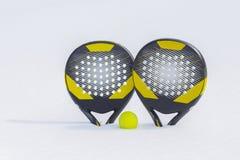 球和两个海滩网球拍在雪随风飘飞的雪被推 库存照片