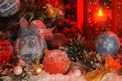 球和圣诞节铃声用雪盖根据在新年` s风景背景的一个红色灯笼  库存照片