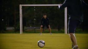 球在前景的草说谎,守门员在门,其他球员解雇球,但是 影视素材