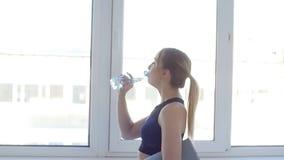 球概念健身pilates放松 在体育活动以后的年轻女人饮用水在白色内部 股票视频
