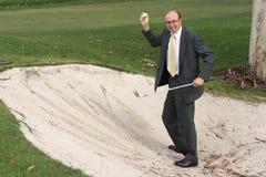 球生意人查找打高尔夫球 免版税库存图片