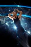 黑球衣的蓝球运动员做在比赛的灌篮 库存图片