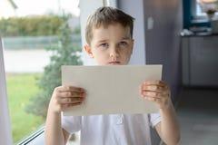 球衣的年轻哀伤的男孩,拿着一张空的copyspace纸片 库存图片