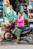 琅勃拉邦,老挝- 2017年1月11日:有一辆摩托车的妇女在城市街道上 垂直 免版税图库摄影