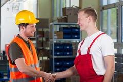 经理与工厂劳工握手 免版税库存图片