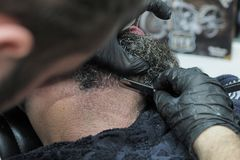 理发师刮一个年长人的胡子有灰色头发锋利的剃刀的 库存照片