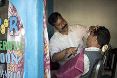 理发师刮脸说谎在头发交谊厅里面的古色古香的理发椅的顾客的胡子 库存图片