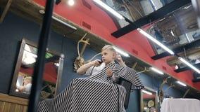 理发师剪她的有剪刀的小客户的头发 大师在理发店,美发师堆积男孩hairdryer的头发 影视素材
