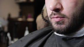 理发师剪客户深色的人的头发有理发师工具的 影视素材