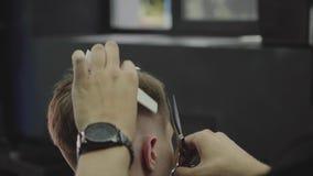 理发师剪客户的头发有剪刀的 ?? 可爱的男性得到在理发店的现代理发 影视素材
