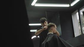 理发师剪客户的头发有剪刀的 可爱的男性得到在理发店的现代理发 ?? 股票录像