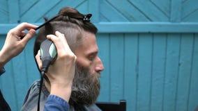 理发师剪客户的头发有电剃刀飞剪机和梳子的 股票视频