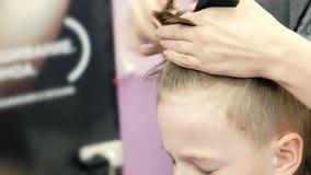 理发师剪有剪刀特写镜头的男孩` s头发 正面图 男孩皱眉 影视素材