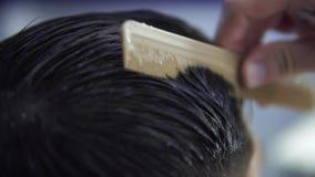 理发师在有刷子的,特写镜头理发店梳客户的湿头发 股票录像
