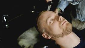 理发师在理发前洗一个有胡子的人的头发 股票视频