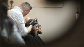 理发师在理发店做与整理者头发剪刀的理发 股票视频